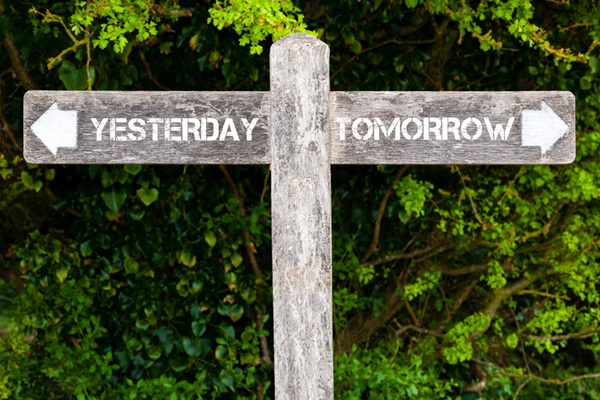 Wooden signpost with two opposite arrows over green leaves background. YESTERDAY versus TOMORROW directional signs, Choice concept image